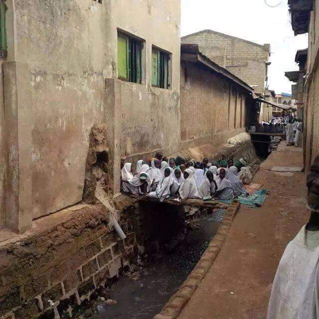 PHOTOS: Almajiri pupils taking Lessons on a drainage in Northern Nigeria