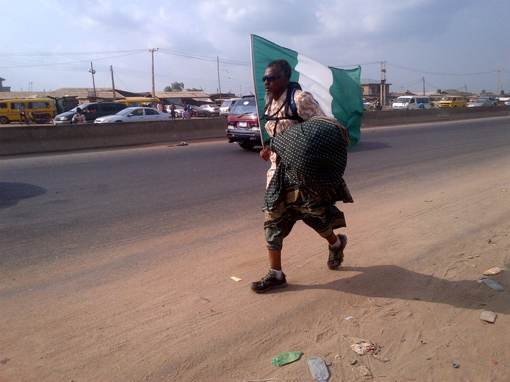 Patriotic Nigerian Seen Carrying A Nigerian Flag Everywhere He Goes