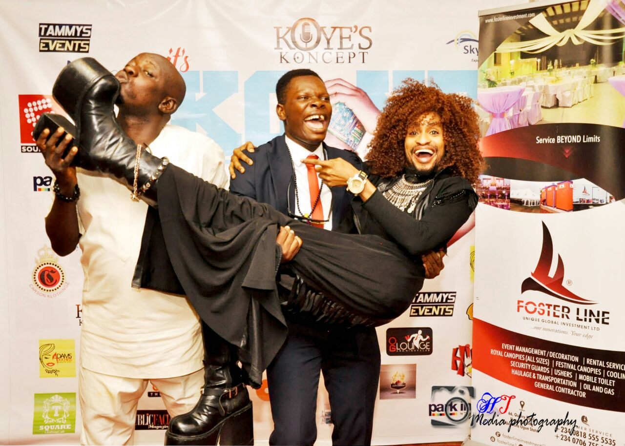 Mr Latin Kissing Denrele's Shoes As Another Man Carries Denrele At An Event In Ogun