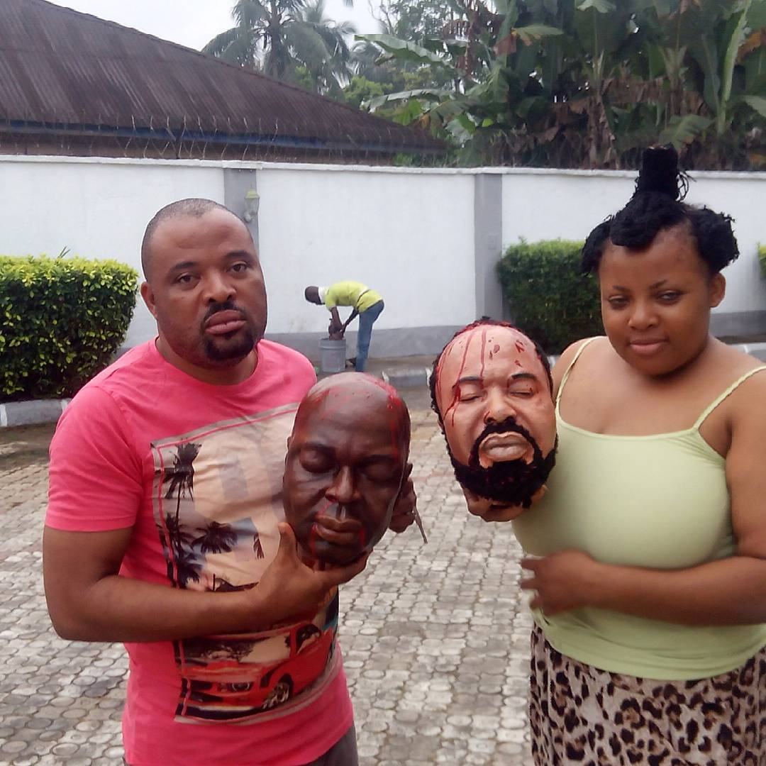 Actors Holding Artificial Heads Of Segun Arinze & Moses Armstrong On Set
