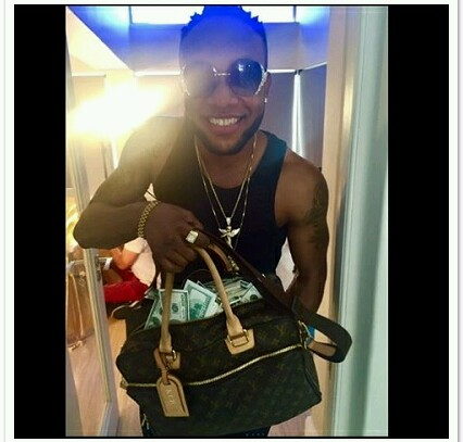 """Keep Talking While I Make Money In Bags"" – Kcee Flaunts Packs Of Dollars In Bag"