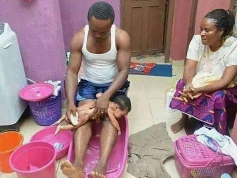 nigerian man pictured bathing his newborn baby photo family nigeria. Black Bedroom Furniture Sets. Home Design Ideas