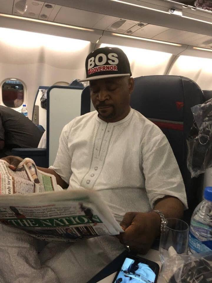 MC Oluomo Pictured On Board A Plane To The US After Attack At Lagos Rally.